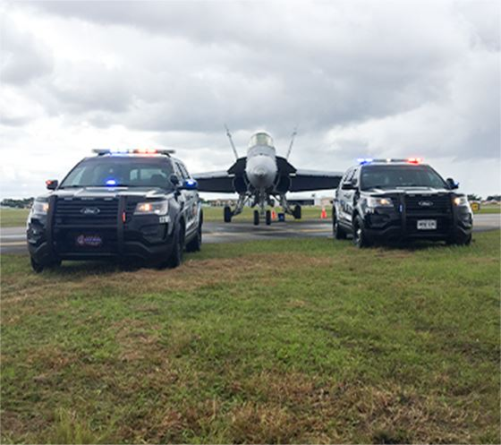 Police vehicles with a plane behind them