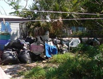 Garbage bags piled high next to residence